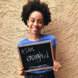 girl holding sign that says I am enough